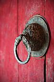 'Ornate Door Handle On A Red Wooden Door; Bhutan'