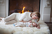 'Mother And Baby On Carpet In Front Of Fireplace; Jordan, Ontario, Canada'