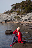 'A Young Woman Sits On A Large Rock On Muckross Lake; Killarney, County Kerry, Ireland'