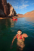 'A Tourist Holding Marine Life In Her Hand In The Water At Espiritu Santo Island; La Paz, Baja, California, Mexico'