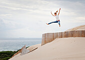 'A Woman Jumps Over A Fence In The Punta Paloma Sand Dunes; Tarifa, Cadiz, Andalusia, Spain'
