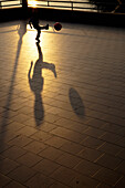 'A Child Kicks A Ball And Has A Large Shadow At Sunset; Camogli, Liguria, Italy'
