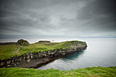 'A Rock Ledge Along The Shoreline Under Dark Clouds; Papey Island, Iceland'