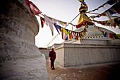 'A Man Walking Amongst The Buildings With Prayer Flags Hanging Above; Kathmandu, Nepal'