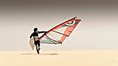 'A Windsurfer Runs On The Sand Of Punta Paloma Beach With His Board; Tarifa, Cadiz, Andalusia, Spain'