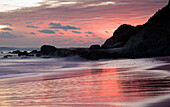 Sunset Over Water At A Rocky Shoreline