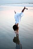 'Puerto Vallarta, Mexico; Girl Doing A Cartwheel On The Beach'