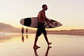 'A Man Walking With His Surfboard On Valdevaqueros Beach; Tarifa Cadiz Andalusia Spain'