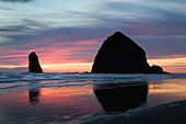 'Silhouette Of Rock Formations And Haystack Rock At Sunset; Cannon Beach, Oregon, United States of America'
