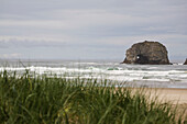 'Rock Formation In The Ocean With Waves On A Grassy Beach; Rockaway Beach, Oregon, United States of America'