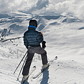 'A Skier Pauses On The Trail To Look Out Over The Mountains; Whistler, British Columbia, Canada'