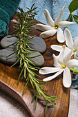 Spa Elements, Flowers, Grey Stones And A Sprig Of Rosemary Ona Wooden Platter With Towels Surrounding.