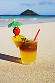 A Mai Tai Garnished With Pinapple And A Strawberry, Sitting In The Sand On The Beach.