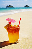 A Mai Tai Garnished With Pinapple And A Cherry, Sitting In The Sand On The Beach.