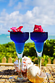 Two Tropical Cocktails Garnished With Flowers In Outdoor Setting.
