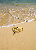 Picture Of A Heart Drawn In The Sand On A Tropical Beach, Yellow Lei Shaped Like A Heart Inside Of Drawing