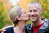 'Wife Kissing Husband On The Cheek In A Park In Autumn; Edmonton, Alberta, Canada'