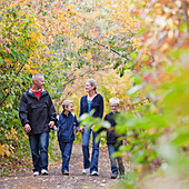 'Family Walking Together On A Path In A Park In Autumn; Edmonton, Alberta, Canada'