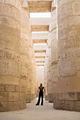 'A Woman Tourist Stands At The Base Of The Massive Columns In The Temples Of Karnak On The East Bank Of Luxor Along The Nile River; Egypt'