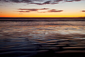 'The Beach At Cox Bay Reflects The Colors Of The Sunset Near Tofino; British Columbia, Canada'