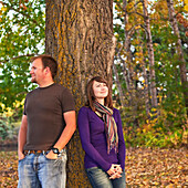 'Young married couple leaning against a tree in a park in autumn;Edmonton alberta canada'