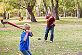 'Father And Son Playing Baseball In A Park; Edmonton, Alberta, Canada'
