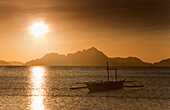 'A Boat Is Silhouetted In The Water At Sunset; Corong Corong, Bacuit Archipelago, Palawan, Philippines'