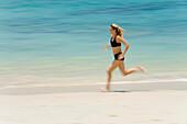'A Woman Tourist Runs Along The Beach On A Tropical Island; Koh Lanta, Thailand'