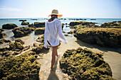 'A Woman Tourist Enjoys The Sunshine On The Beach Of A Tropical Island; Koh Lanta, Thailand'