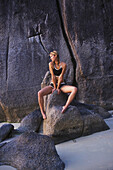 'An Attractive Blond Haired Woman Sits On Rocks On The Beach Of A Tropical Island; Koh Tao, Thailand'