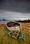 'A Weathered Boat And Fishing Equipment Sitting On The Shore With Lindisfarne Castle In The Distance; Lindisfarne, Northumberland, England'