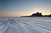 'Sand Blowing Across The Beach With Bamburgh Castle In The Distance At Sunset; Bamburgh, Northumberland, England'