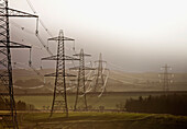 'Electrical Transmission Towers And Lines In A Row Across Fields; Northumberland, England'
