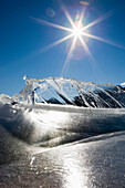 'Ice Formations On A Frozen Lake Shoreline In The Mountains With A Sunburst And Blue Sky; Alberta, Canada'