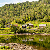 'Houses In A Valley Beside A Tree Covered Hill And Tranquil Water; Bergen, Norway'