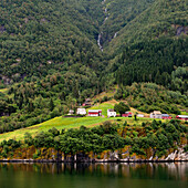 'Houses At The Base Of A Tree Covered Mountain Along The Water's Edge; Granvin, Norway'