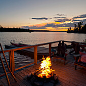 'Burning Fire On A Wooden Dock Along The Water's Edge At Sunset; Lake Of The Woods, Ontario, Canada'