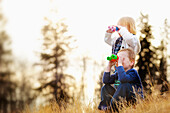 'A Young Boy And Girl Looking Through Binoculars; Spruce Grove, Alberta, Canada'
