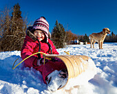 'A Young Girl Sits On A Toboggan In The Snow With A Dog In The Background; Spruce Grove, Alberta, Canada'