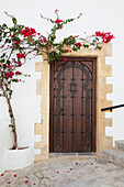 'Wooden Door On A White Building With A Blossoming Vine Growing On The Wall; Vejer De La Frontera, Andalusia, Spain'