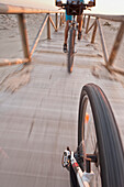 'Cyclists Ride Down A Wooden Boardwalk On The Beach; Tarifa, Cadiz, Andalusia, Spain'