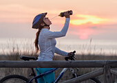 'A Cyclist Stops For A Drink On A Wooden Boardwalk Along The Ocean; Tarifa, Cadiz, Andalusia, Spain'