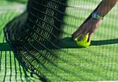 'Retrieving A Tennis Ball By The Net; Tarifa, Cadiz, Andalusia, Spain'