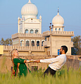 'A Mixed Race Couple Holding Hands In A Field With A Temple In The Background; Ludhiana, Punjab, India'
