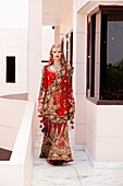 'A Bride In An Ornate Red And Gold Gown Walking Down A Corridor; Ludhiana, Punjab, India'