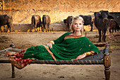 'Portrait Of A Blond Woman Wearing A Sari And Laying On A Hammock With Cattle In The Background; Ludhiana, Punjab, India'