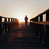 'Silhouette Of A Person Walking On A Wooden Boardwalk Towards The Beach And Ocean; Tarifa, Cadiz, Andalusia, Spain'