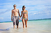 'A Couple Walking In The Shallow Water Along The Beach Holding Hands; Punta Cana, La Altagracia, Dominican Republic'