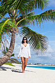 'A Woman In A White Dress Walking Beside A Palm Tree On A White Sand Beach; Punta Cana, La Altagracia, Dominican Republic'