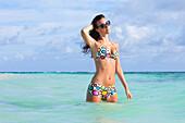 'A Woman Standing In The Ocean Wearing A Colourful Bikini And Sunglasses; Punta Cana, La Altagracia, Dominican Republic'